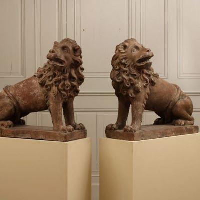 Paire de lions stylisés assis en terre cuite