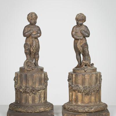 Paire de terres cuites représentant deux putti debout chacun sur un fût de colonne.