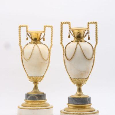 Une paire d'urnes en marbre de carrare montées en bougeoirs