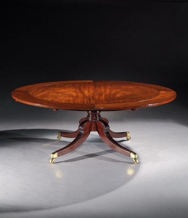 A REGENCY MAHOGANY CIRCULAR EXTENDING DINING TABLE