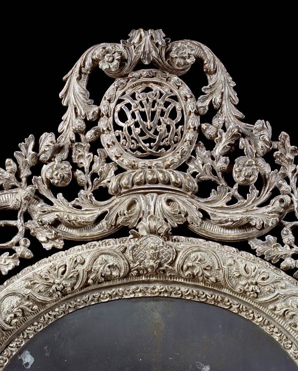 A WILLIAM III OVAL SILVERED GESSO MIRROR IN THE MANNER OF DANIEL MAROT