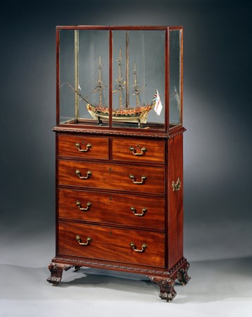 A GEORGE III MAHOGANY CASED SHIP MODEL ON A CHEST STAND. THE CASE AND CHEST ATTRIBUTED TO WILLIAM VILE.