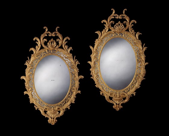 A MAGNIFICENT PAIR OF GEORGE III CARVED GILTWOOD OVAL MIRRORS