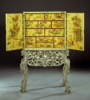 A CHARLES II CREAM JAPANNED CABINET ON SILVERED STAND