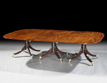 A GEORGE III MAHOGANY THREE PILLAR DINING TABLE