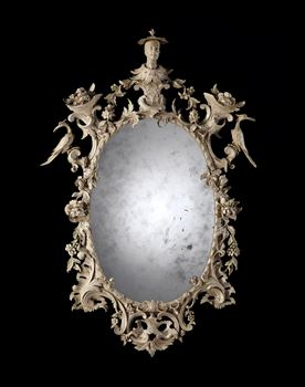 A GEORGE III PAINTED LIMEWOOD OVAL MIRROR ATTRIBUTED TO THOMAS JOHNSON