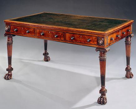 A REGENCY CARVED MAHOGANY AND EBONY WRITING TABLE