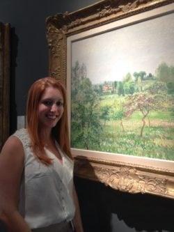 Arts PR guru Miss Chloe Nelkin with a landscape by Camille Pissarro at Galerie B. Weil's stand A29 at Masterpiece Fair 2014.