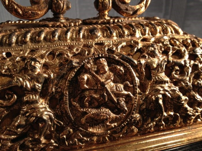 Detail of gilded basket top of a bracket clock by Merriman, with St George and the Dragon centre. Raffety Antique Clocks