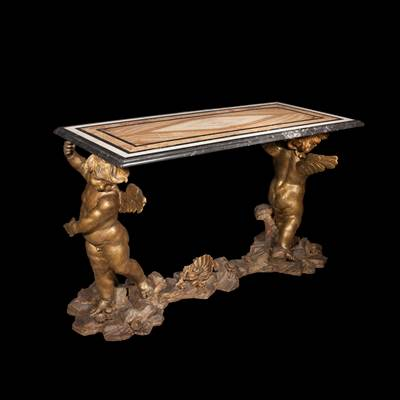 A carved and gilded wood console with putti, the top with